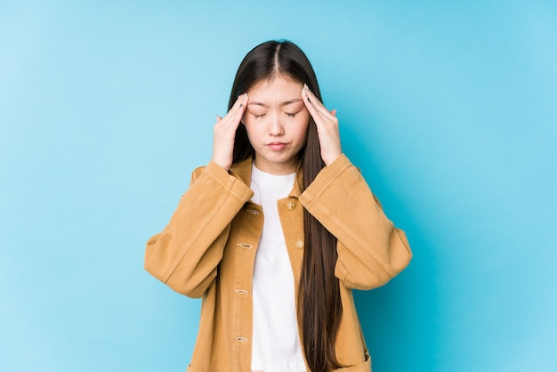 Jonge chinese vrouw poseren in een blauwe muur geïsoleerd tempels aanraken en hoofdpijn hebben.
