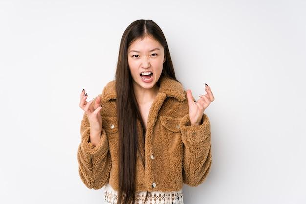 Jonge chinese vrouw poseren in een witte muur geïsoleerd boos schreeuwen met gespannen handen.