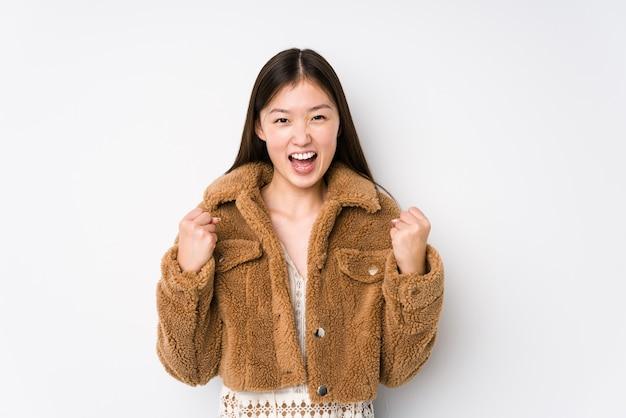 Jonge chinese vrouw poseren in een witte muur geïsoleerd onbezorgd en opgewonden juichen. overwinning concept.