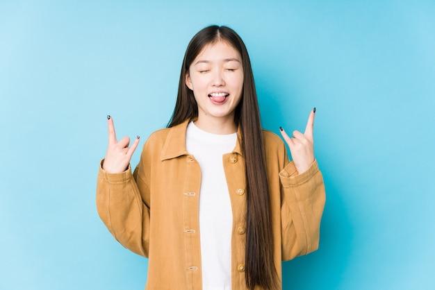Jonge chinese vrouw poseren op een blauwe achtergrond geïsoleerd met rock gebaar met vingers
