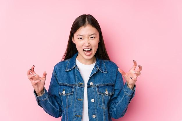 Jonge chinese vrouw poseren op roze geïsoleerd schreeuwen van woede.