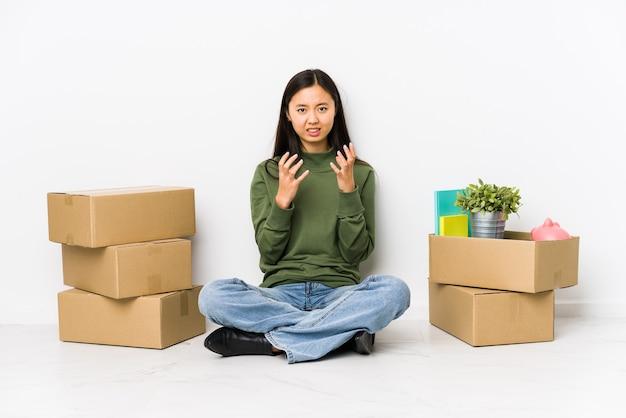 Jonge chinese vrouw verhuizen naar een nieuw huis boos schreeuwen met gespannen handen.