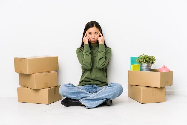 Jonge chinese vrouw verhuizen naar een nieuw huis gericht op een taak, wijsvingers hoofd houden.