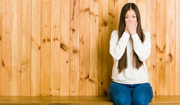 Jonge chinese vrouwenzitting op een houten geschokte plaats behandelend mond met handen.