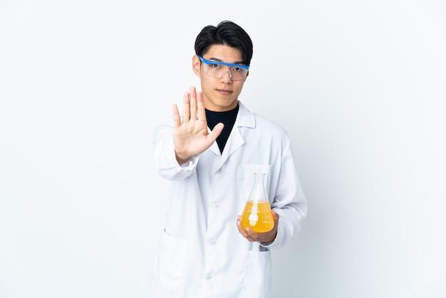 Jonge chinese wetenschappelijke man geïsoleerd op een witte muur stop gebaar maken