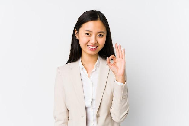 Jonge chinese zakenvrouw geïsoleerd vrolijk en zelfverzekerd tonend ok gebaar.