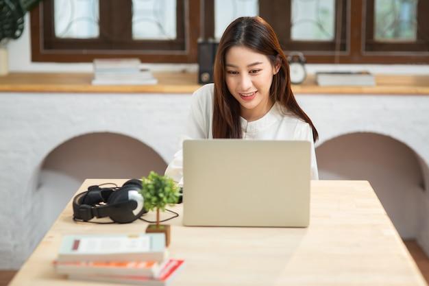 Jonge chinese zakenvrouw werken met internet met behulp van computer zitten in appartement