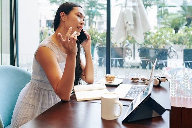 Jonge chinese zakenvrouw zittend aan tafel met tablet en laptop en telefoneren met collega