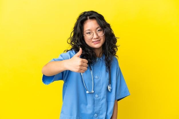 Jonge chirurg arts aziatische vrouw geïsoleerd op gele achtergrond met duimen omhoog omdat er iets goeds is gebeurd