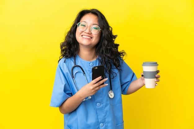 Jonge chirurg arts aziatische vrouw geïsoleerd op gele achtergrond met koffie om mee te nemen en een mobiel