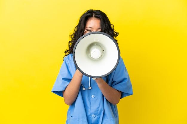 Jonge chirurg arts aziatische vrouw geïsoleerd op gele achtergrond schreeuwen door een megafoon