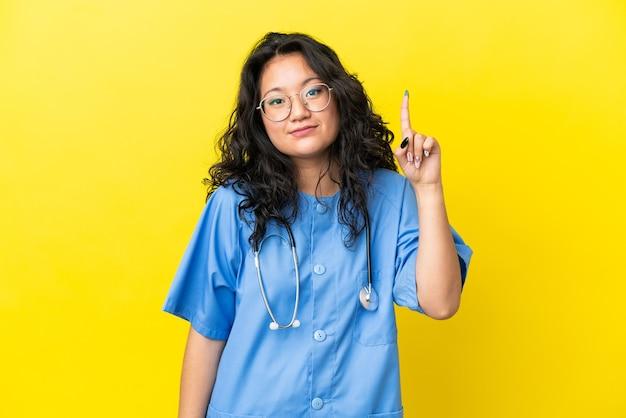 Jonge chirurg arts aziatische vrouw geïsoleerd op gele achtergrond wijzend met de wijsvinger een geweldig idee