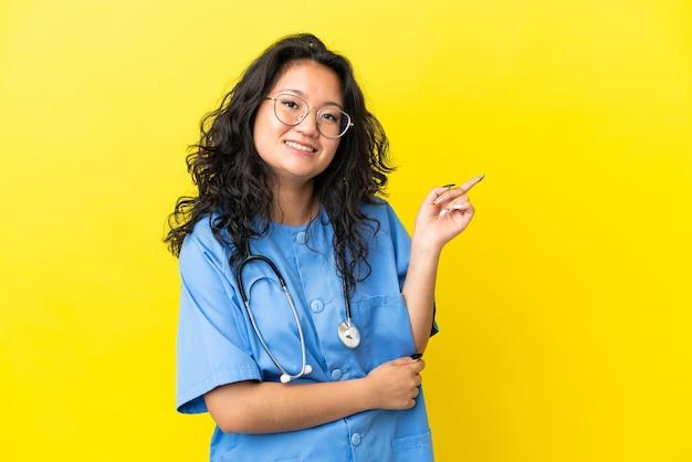 Jonge chirurg arts aziatische vrouw geïsoleerd op gele achtergrond wijzende vinger naar de zijkant