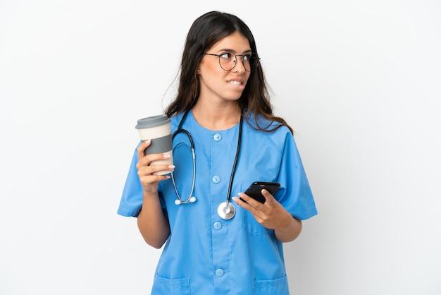 Jonge chirurg arts kaukasische vrouw geïsoleerd op een witte achtergrond met koffie om mee te nemen en een mobiel terwijl ze iets denkt