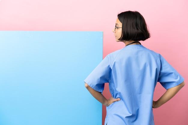 Jonge chirurg van gemengd ras met een groot spandoek over geïsoleerde achtergrond in de achterste positie en opzij kijkend