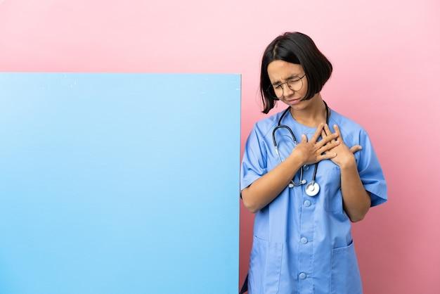 Jonge chirurg van gemengd ras met een groot spandoek over geïsoleerde achtergrond met pijn in het hart