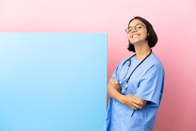 Jonge chirurg vrouw van gemengd ras met een groot spandoek over geïsoleerde achtergrond met gekruiste armen en kijken ernaar uit