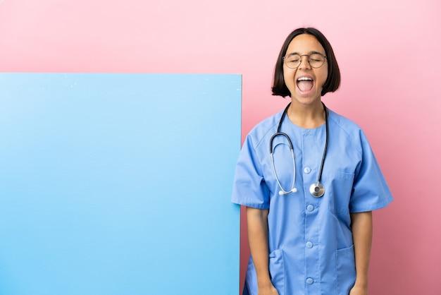 Jonge chirurgenvrouw van gemengd ras met een groot spandoek over een geïsoleerde achtergrond die naar voren schreeuwt met wijd open mond