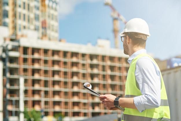 Jonge civiel ingenieur die helm draagt die bouwwerftechniek en architectuurconcept inspecteert