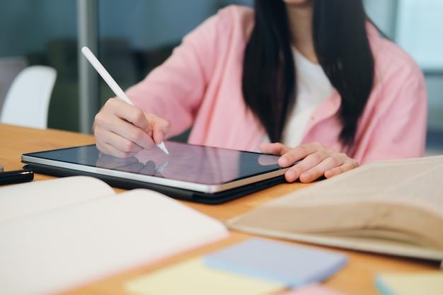 Jonge collage student met behulp van computer en mobiel apparaat online studeren. onderwijs en online leren.