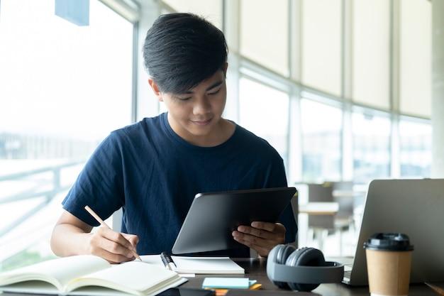 Jonge collage student met behulp van computer en mobiel apparaat online studeren.