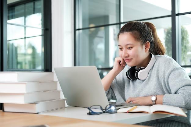 Jonge collagestudent die computer en mobiel apparaat gebruikt die online studeert. onderwijs en online leren.
