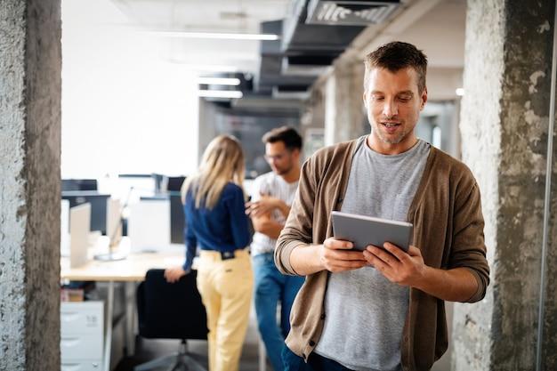 Jonge collega man met behulp van technologie, digitale tablet in zakelijk kantoor