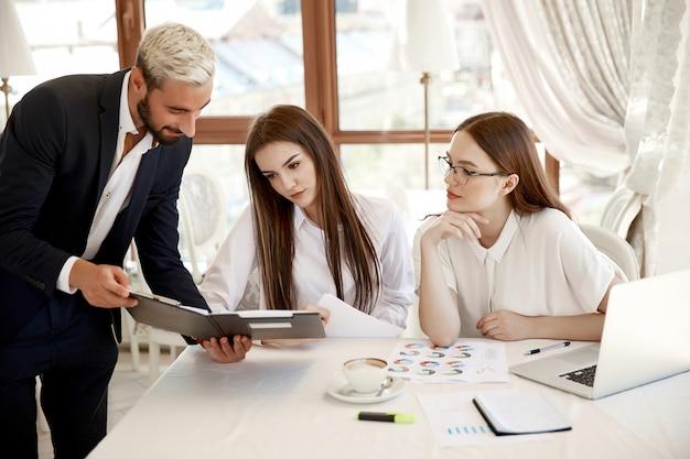 Jonge collega's bespreken jaarlijkse financiële rapporten en diagrammen