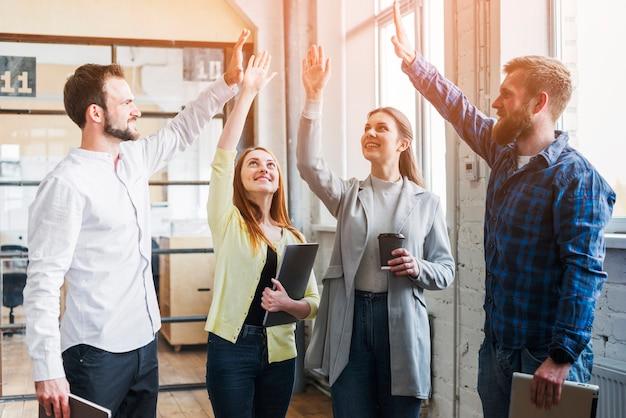 Jonge collega's geven high five aan elkaar