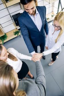 Jonge collega's handen samenstellen als symbool van eenheid in het kantoor