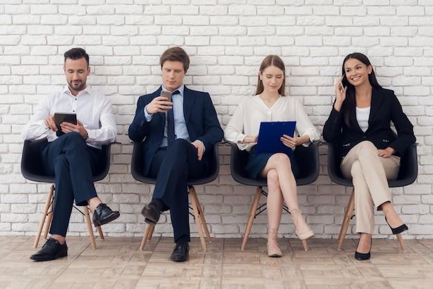 Jonge collega's in elegante pakken zitten op zwarte stoelen.