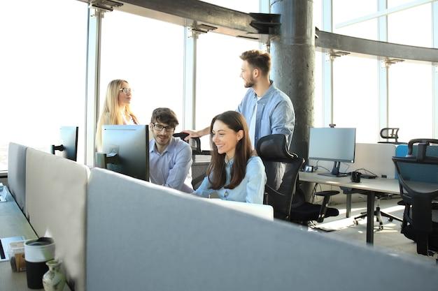 Jonge collega's in nette vrijetijdskleding die werken terwijl ze tijd op kantoor doorbrengen.
