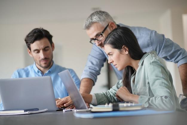 Jonge collega's met oudere baas werken met computers