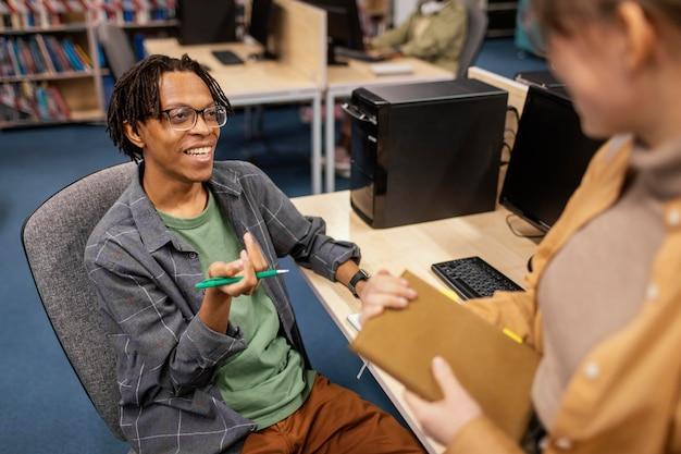 Jonge collega's praten in de bibliotheek