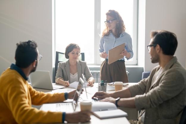 Jonge collega's zitten aan tafel en bespreken projectplan aangeboden door mooie dame met klembord op personeelsvergadering