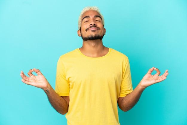 Jonge colombiaanse knappe man geïsoleerd op blauwe achtergrond in zen pose