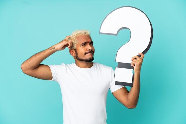 Jonge colombiaanse knappe man geïsoleerd op blauwe achtergrond met een vraagtekenpictogram en twijfels