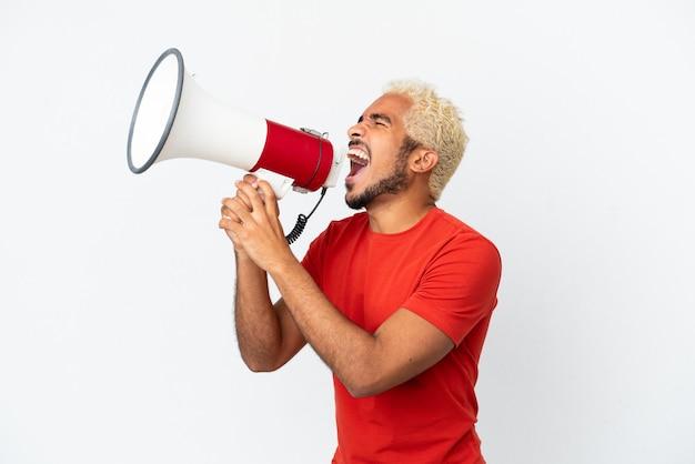 Jonge colombiaanse knappe man geïsoleerd op een witte achtergrond die door een megafoon schreeuwt om iets in zijpositie aan te kondigen