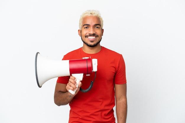 Jonge colombiaanse knappe man geïsoleerd op een witte achtergrond die een megafoon vasthoudt en veel lacht