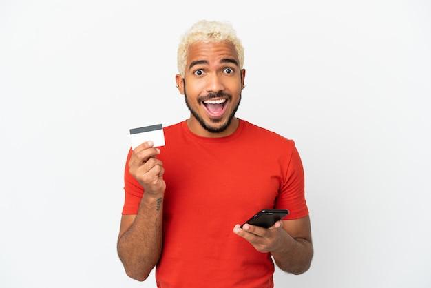 Jonge colombiaanse knappe man geïsoleerd op een witte achtergrond die met de mobiel koopt en een creditcard vasthoudt met een verbaasde uitdrukking
