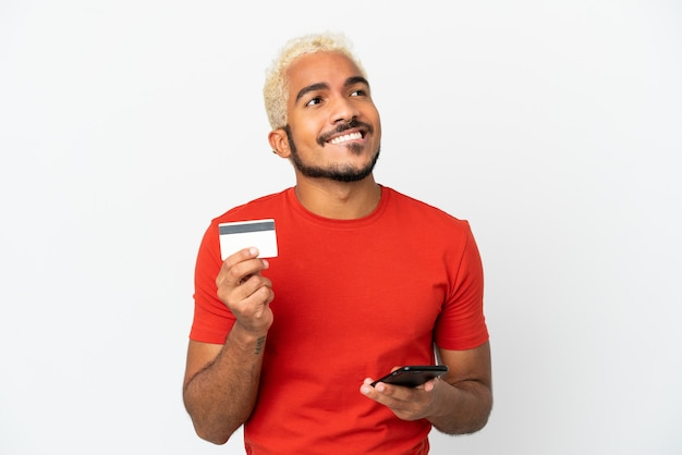Jonge colombiaanse knappe man geïsoleerd op een witte achtergrond kopen met de mobiel met een creditcard terwijl hij denkt