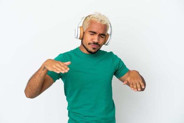 Jonge colombiaanse knappe man geïsoleerd op een witte achtergrond muziek luisteren en dansen