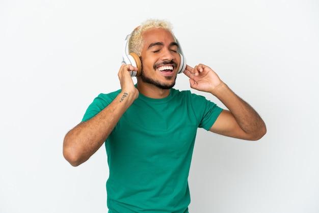 Jonge colombiaanse knappe man geïsoleerd op een witte achtergrond muziek luisteren en zingen