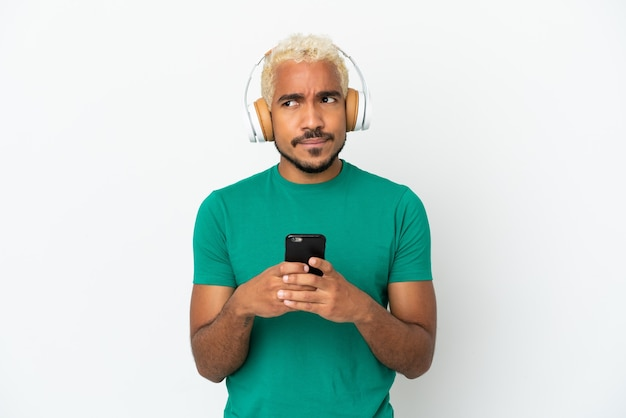 Jonge colombiaanse knappe man geïsoleerd op een witte achtergrond muziek luisteren met een mobiel en denken