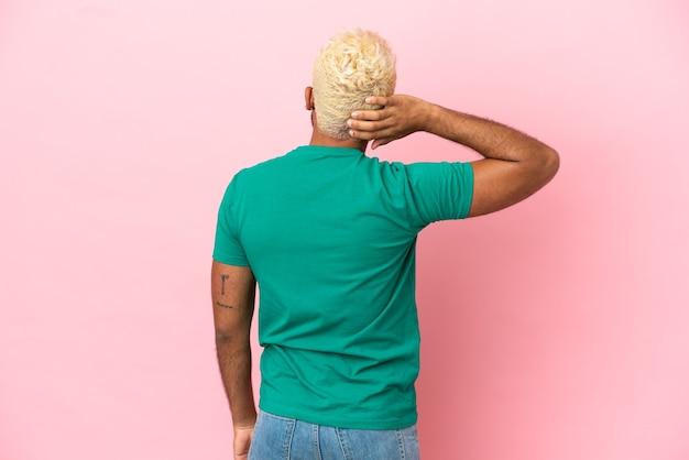 Jonge colombiaanse knappe man geïsoleerd op roze achtergrond in achterpositie en denken
