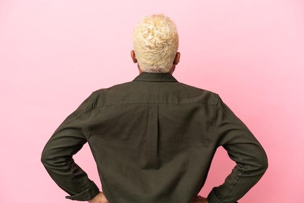 Jonge colombiaanse knappe man geïsoleerd op roze achtergrond in achterpositie