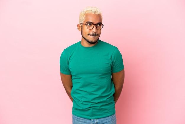 Jonge colombiaanse knappe man geïsoleerd op roze achtergrond met twijfels tijdens het opzoeken