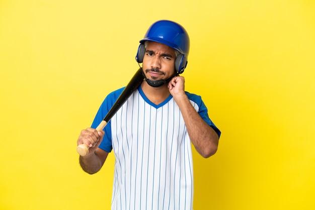 Jonge colombiaanse latijns-man die honkbal speelt geïsoleerd op gele achtergrond met twijfels