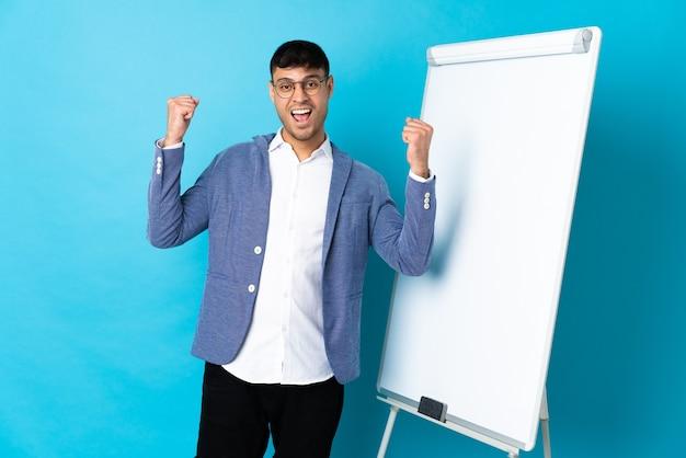 Jonge colombiaanse man geïsoleerd op blauw geeft een presentatie op wit bord en viert een overwinning
