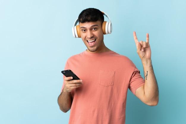 Jonge colombiaanse man geïsoleerd op blauw luisteren muziek met een mobiele rock gebaar maken